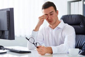 man rubbing eyes due to dry eye syndrome and blepharitis in Sunrise